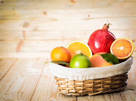 Small wicker basket of delicious assorted fresh fruit with an apple and a variety of citrus including a juicy halved orange on a wooden background photo