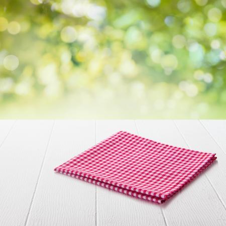 wooden desk: Netjes opgevouwen verse rode en witte gecontroleerd doek conceptuele van een land of een rustieke ambiance op een tuintafel in een zonnige zomer tuin met focus op het servet