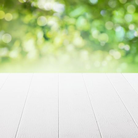太陽の下で空のテーブル テーブルの上に、フォア グラウンドでに焦点を当てた製品の配置のための夏の庭を浸した