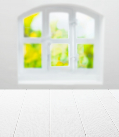 Empty clean white kitchen table in front of a cottage pane arched window with a view of greenery in summer sunshine as a background for product placement