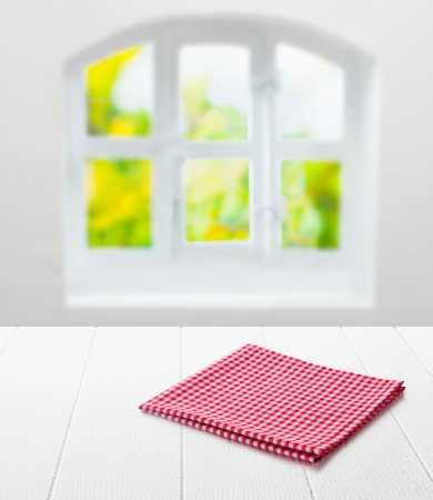 product placement: Red and white checked cloth neatly folded on top of an empty clean white table top under a window with a view of summer greenery in a country kitchen