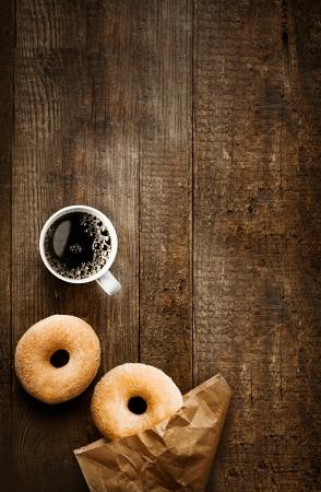 Bovenaanzicht van twee verleidelijke verse gesuikerde donuts met hun bruine papieren verpakking en een kop sterke zwarte filter of espresso koffie op een rustieke houten tafel Stockfoto