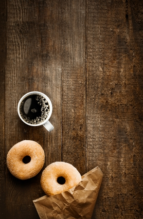 Overhead view of two tempting fresh sugared doughnuts with their brown paper wrapping and a cup of strong black filter or espresso coffee on a rustic wood table