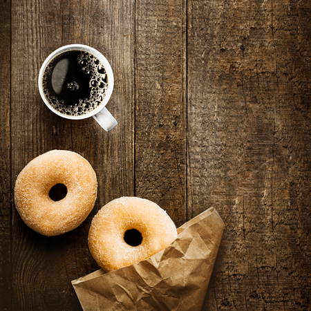 top angle view: Close up overhead view of two delicious sugared ring doughnut with espresso coffee and crumpled brown paper packet on a rustic wooden surface with copyspace for a relaxing coffee break
