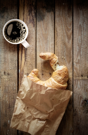 Fresh flaky golden croissant with a bite missing and a cup of strong black espresso coffee on an old wooden background with copyspace, overhead view photo