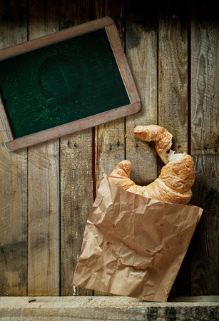 Overhead view of a freshly baked golden croissant, a cup of full roast espresso coffee and an old blank school slate for a menu or text on rustic wooden boards photo