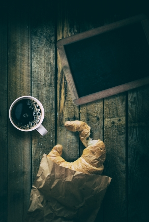Overhead view of a vintage blank school slate with a cup of strong black espresso coffee and a crescent shaped crispy croissant with a bite missing in a crumpled bag photo