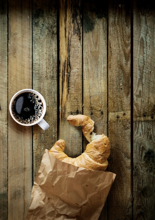 Coffee break in the country with a cup of freshly brewed espresso coffee and a bitten croissant in a crumpled brown paper bag on a grungy weathered table top with copyspace photo