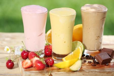Strawberry smoothie: Tre deliziosi frullati con yogurt o miscela di gelato, due a base di frutta e uno di cioccolato, insieme con varie frutta fresca tropicale su un tavolo da giardino Archivio Fotografico