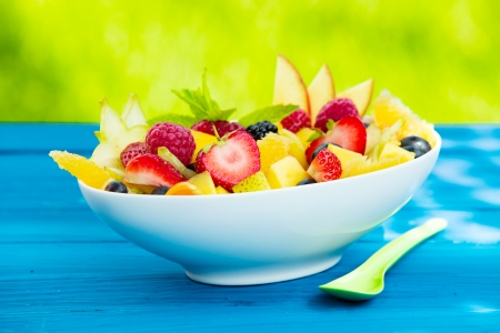 fruity salad: Bowl of colourful tasty tropical fruit salad made with a selection of ripe fruit including strawbwerries, raspberries, apples and citrus topped with a sprig of mint