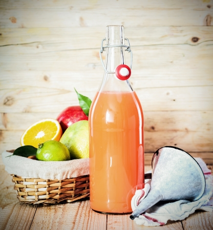 facilitate: Fresh tropical fruit juice in a glass bottle alongside a basket of assorted fruit used as ingredients and a small metal funnel to facilitate pouring Stock Photo