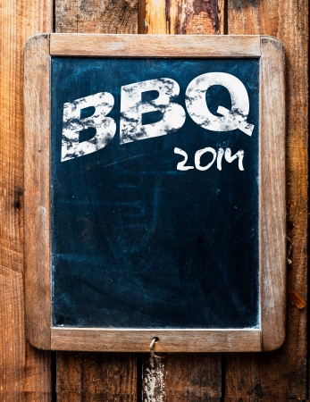 bbq background: Old grunge BBQ advertising sign on an old school slate board with a distressed wooden frame and copyspace for your text mounted on wooden boards Stock Photo