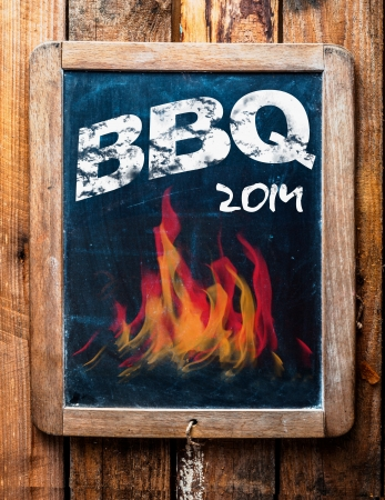 Rustic advertisement for a BBQ on a vintage kids school slate with a picture of red hot flames and an annotation at the bottom saying - Mans stuff photo
