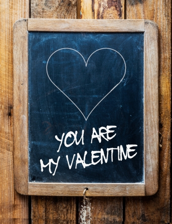 heartfelt: Valentines message on an old retro school slate in a rustic weathered wooden frame saying - You are my Valentine - under a simple hand drawn outline of a heart for a heartfelt tender greeting