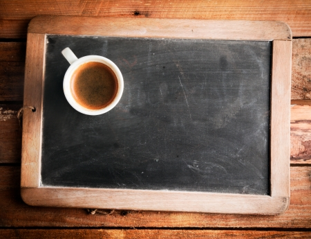 Overhead view of a cup of coffee on an old school slate with a wooden frame and blank copyspace on the cleaned chalkboard lying on a rustic wooden table photo