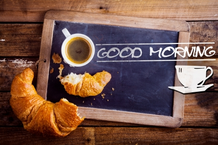 Good morning sign with a cup of fresh hot morning coffee and a broken croissant on an old school slate with a distressed wooden frame on a rustic table