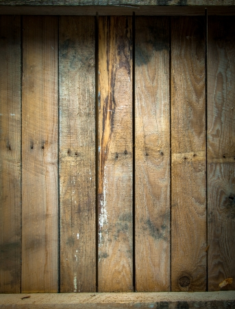 Background texture of a grungy stained and weathered wooden table top with a line of old nails and parallel vertical planks photo