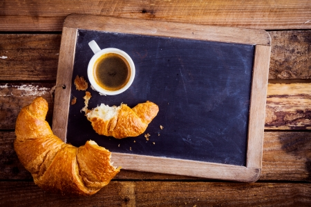 Overhead view of a fresh cup of coffee and a flaky croissant broken in two on an old school slate over a rustic wooden background, copyspace on the slate