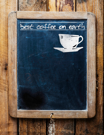 Old restaurant or coffee house menu on a rustic weathered old vintage school slate with a silhouette of a cup and the text - best coffee on earth and blank copyspace photo