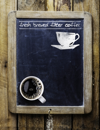 old bar: Fresh brewed filter coffee - handwritten on an old vintage school slate used as an advertising sign in a rustic coffee shop with a fresh cup of aromatic coffee in the bottom corner
