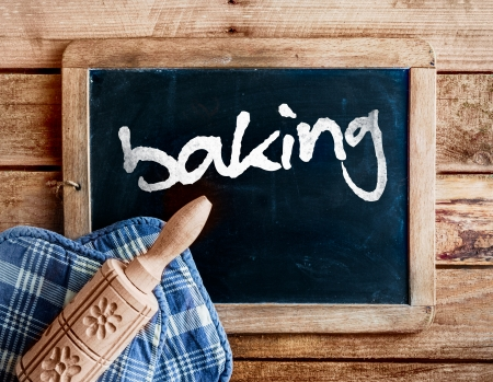 Country kitchen with a decorative carved wooden rolling pin with a floral pattern on oven gloves lying on an old vintage school slate with a distressed wooden frame with the handwritten word - baking