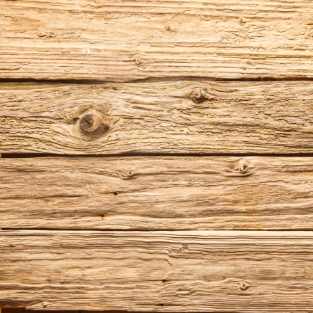 Old rough rustic wooden background texture with aged and weathered boards with a distressed surface and knots in closeup detail photo
