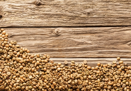 top down: Coffee bean border with raw brown fresh dried beans arranged along the bottom of the frame on weathered rough textured rustic wood with copyspace