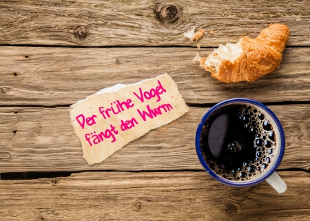 Der frühe Vogel fängt den Wurm - the early bird catches the worm - an inspirational message on a torn piece of paper alonside an early breakfast of espresso coffee and half eaten croissant