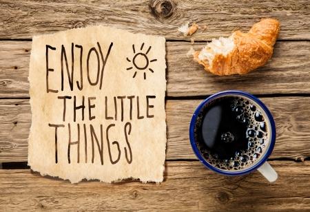 Inspirado desayuno temprano por la mañana de un croissant recién hecho a medio comer con café de filtro y una nota escrita a mano - Disfrute de las pequeñas cosas - que nos recuerda a apreciar incluso los momentos simples de la vida