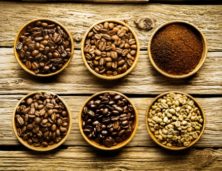 Five varieties of coffee beans and ground powder is separate dishes showing the different strengths and colour of the beans from raw through medium to full roast on a weathered driftwood background