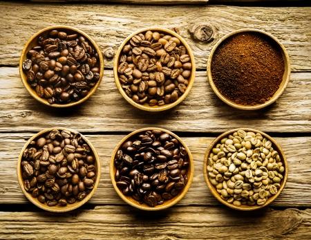 Vijf soorten koffiebonen en gemalen poeder is aparte gerechten met de verschillende sterktes en de kleur van de bonen van rauwe tot medium tot volledige gebraden op een verweerde drijfhout achtergrond Stockfoto