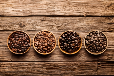 brew house: Assorted raw and roasted coffee beans in small individual containers on a rustic, weathered textured driftwood background, overhead view with copyspace
