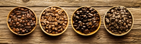 Selection of four different fresh dried roasted coffee beans in individual containers arranged in a line viewed from above on a textured driftwood background