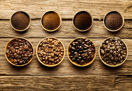 overhead view: Preparing fresh roast coffee beans to brew with an overhead view of four different varieties of beans with their corresponding ground powder in small dishes on a weathered driftwood background