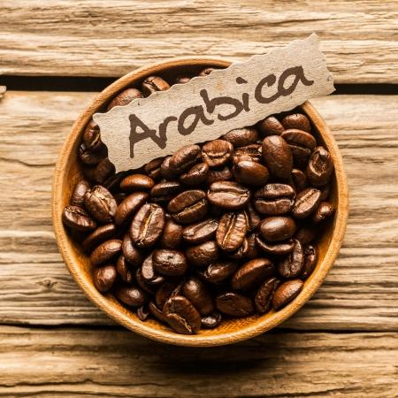 古い木製のテーブルの上のアラビカ種のコーヒー豆の完全ボウルのクローズ アップ