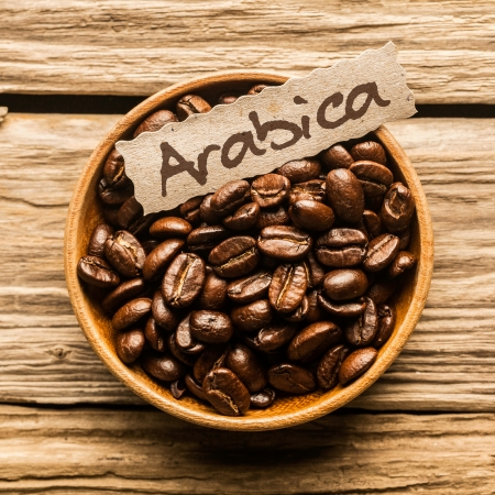 Close up of a bowl full of Arabica coffee beans over an old wooden table