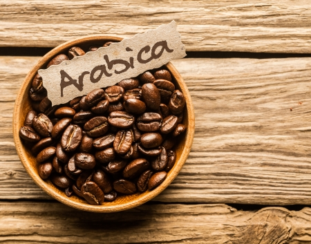 arabica: Bowl full of Arabica coffee beans over an old wooden table Stock Photo