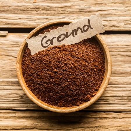 in ground: Primo piano di una ciotola piena di caff� macinato su un vecchio tavolo di legno