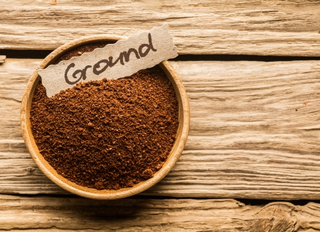 brew house: bowl full of ground coffee over an old wooden table Stock Photo