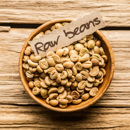 Close up of a bowl of raw coffee beans over an old wooden table photo