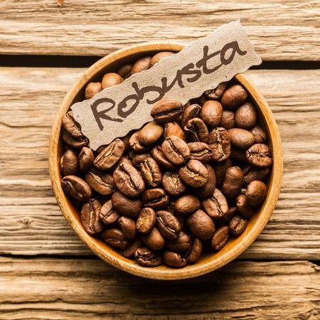 닫기 오래 된 나무 테이블에 로부스타 커피 콩의 그릇의 최대