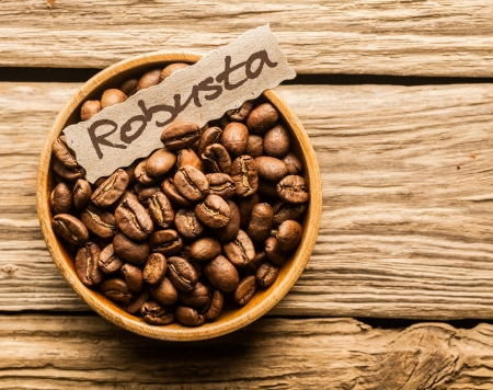 robusta: Bowl of Robusta coffee beans over an old wooden table Stock Photo