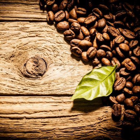 vignetting: Full roast coffee beans with a fresh green leaf aarranged as a corner border on a square format image over knotty weathered wooden boards with copyspace and vignetting