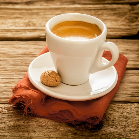 Cup of delicious freshly brewed espresso coffee served in a plain white cup and saucer with a macaroon on a grungy weathered rustic wooden surface, close up square format photo