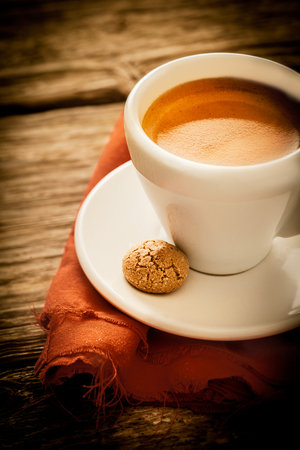Morning coffee break with a cup of aromatic rich frothy espresso and a macaroon served in a rustic kitchen on a weathered old wooden surface, closeup high angle view photo