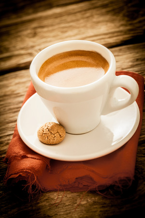 Freshly brewed espresso coffee in a country kitchen served in a plain white cup and saucer with a tasty macaroon for a refreshing morning beverage, with copyspace and vignetting photo