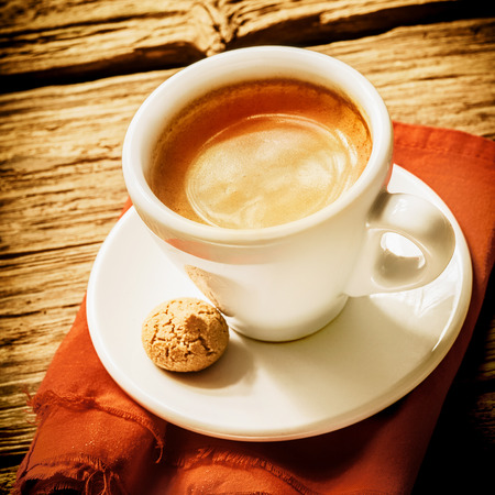 White cup of foamy coffee on a saucer with a mini biscuit, on a coral kitchen towel, on a rustic wooden table photo
