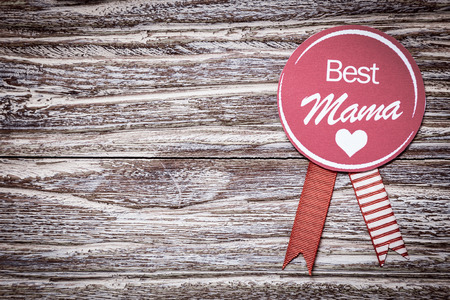 woodgrain: Round purple rosette with the text Best Mama for a loving mothers day or baby shower greeting celebrating a special mother on a grunge weathered wood background with copyspace