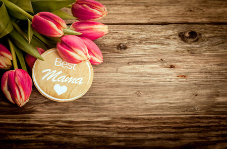 fx: Best Mama greeting card on grunge rustic wood with a bunch of fresh red tulips in the corner and copyspace for your text on Mothers Day or for a Baby Shower Stock Photo