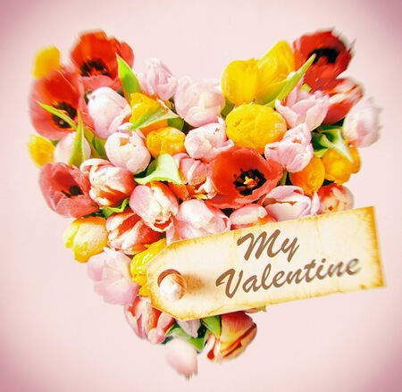 Tender feminine Valentines greeting card with a - My Valentine - gift tag on a heart of colourful decorative fresh tulips on a square pink background with vignetting photo